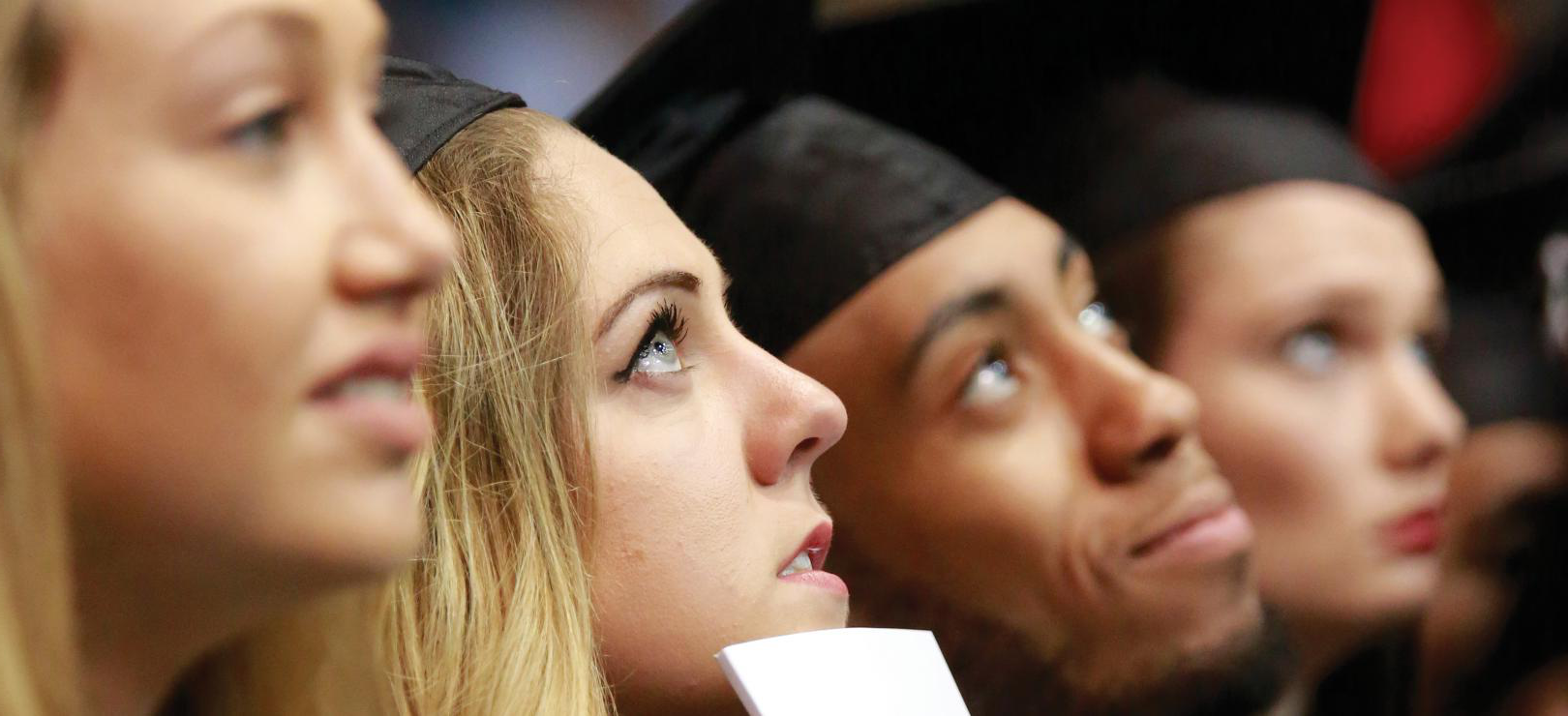 Image of students in Commencement caps and gowns, listening to unseen speaker