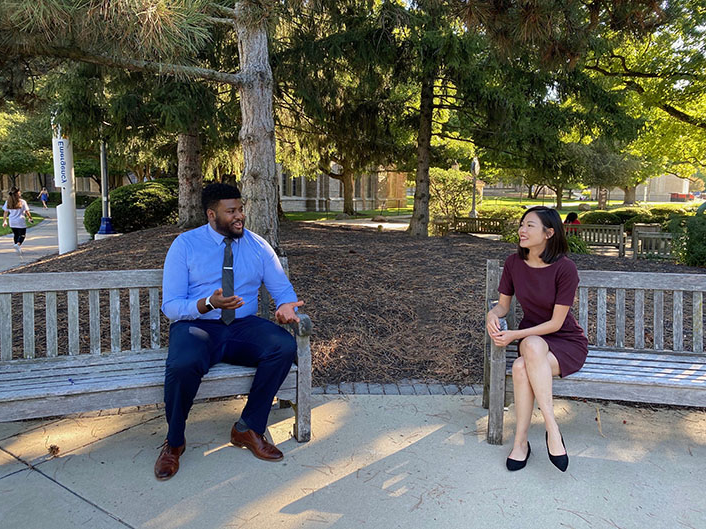 Two people sitting on a bench talking.