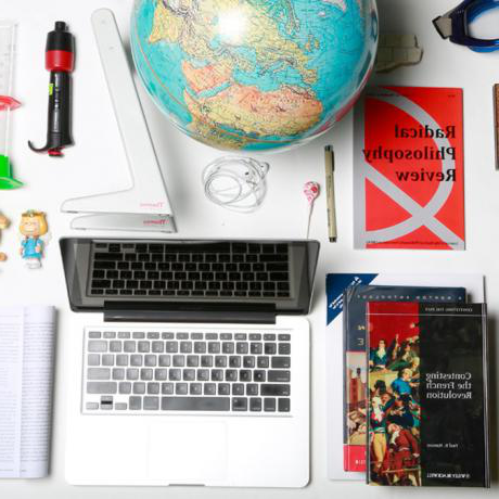 A laptop, books, a globe, and other assorted items arranged on a flat white surface